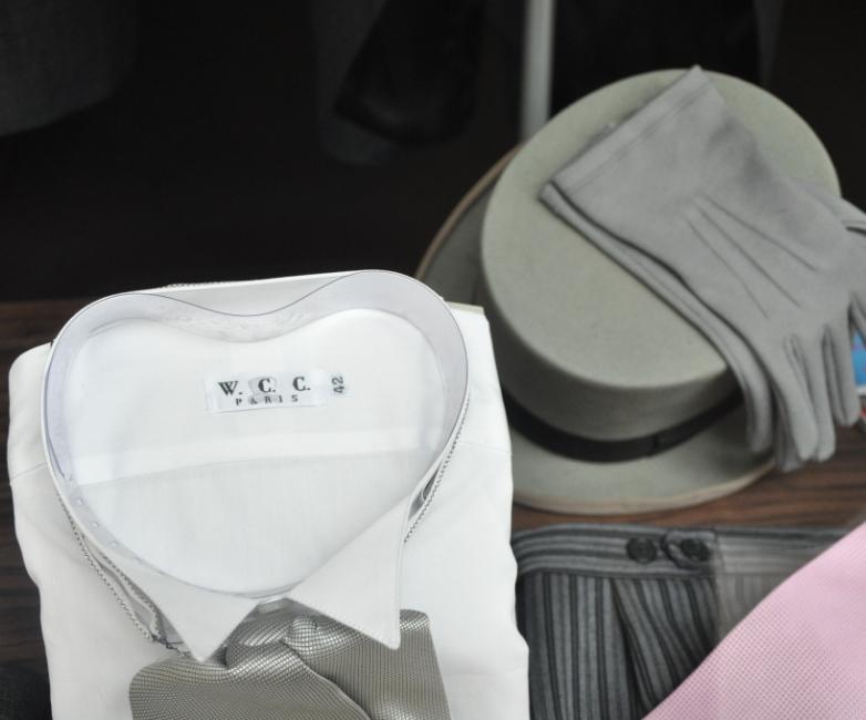 Une chemise à col cassé, sa lavallière, un chapeau haute-forme, un pantalon rayé et des gants gris pour les mariages