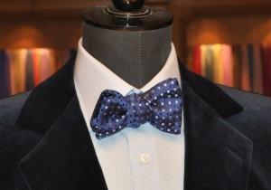 Un noeud papillon Charvet, sur une chemise finement rayée et une veste en velours bleu