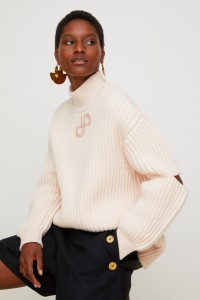Le logo JP… Si une marque peut sans honte se permettre le logo, c'est bien Patou... Pull oversize en laine Mérinos à découpes, couleur fleur de pêche